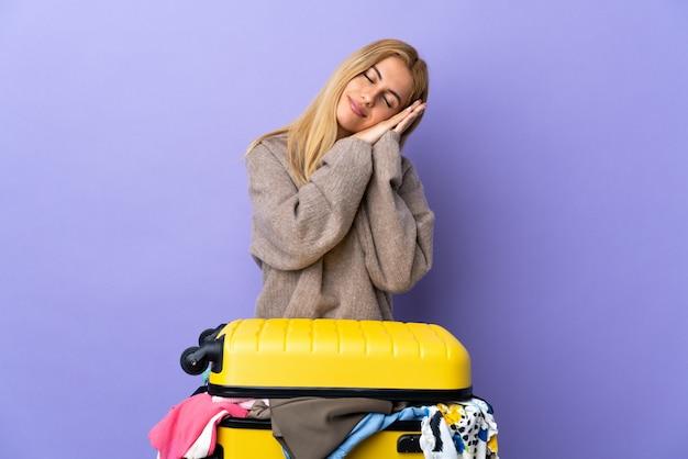 Jonge uruguayaanse blondevrouw met een koffer vol kleren over geïsoleerde purpere muur die slaapgebaar in dorable uitdrukking maken