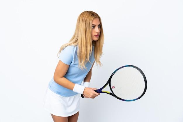 Jonge uruguayaanse blondevrouw over geïsoleerd wit muur speeltennis