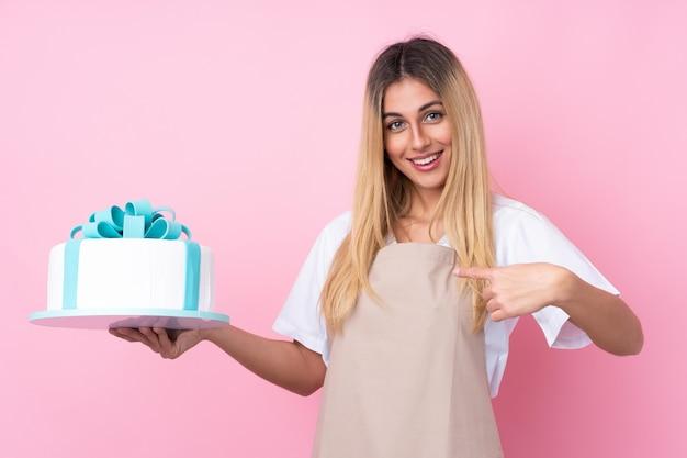 Jonge uruguayaanse gebakjevrouw met een grote cake met verrassingsgelaatsuitdrukking