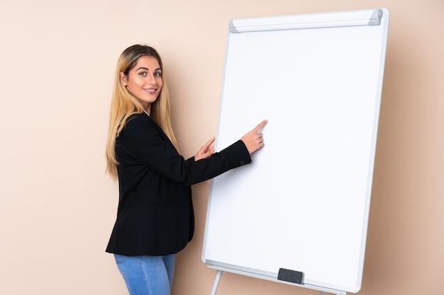 Jonge uruguayaanse vrouw die een presentatie op wit bord geeft en erin schrijft