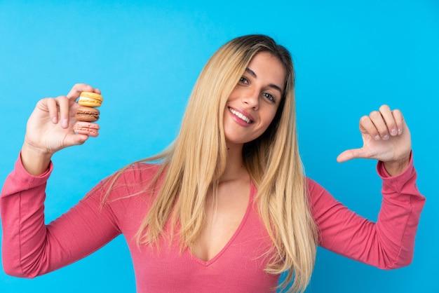 Jonge uruguayaanse vrouw die kleurrijke franse macarons houdt en trots