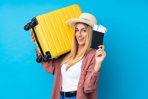 Jonge uruguayaanse vrouw in vakantie met koffer en paspoort en verrast