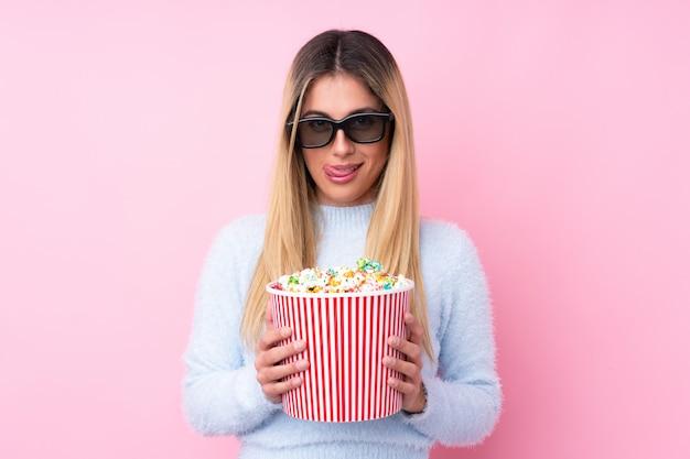 Jonge uruguayaanse vrouw met 3d glazen en een grote emmer popcorns houden