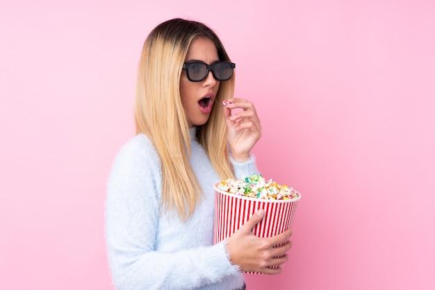 Jonge uruguayaanse vrouw met 3d glazen en het houden van een grote emmer popcorns terwijl het kijken kant