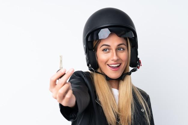 Jonge uruguayaanse vrouw met een motorhelm over geïsoleerde witte muur