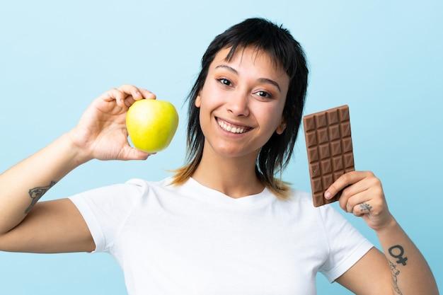 Jonge uruguayaanse vrouw over geïsoleerde blauwe achtergrond die een chocoladetablet in de ene hand en een appel in de andere