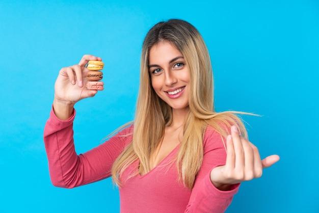 Jonge uruguayaanse vrouw over geïsoleerde blauwe muur die kleurrijke franse macarons houdt en uitnodigt te komen