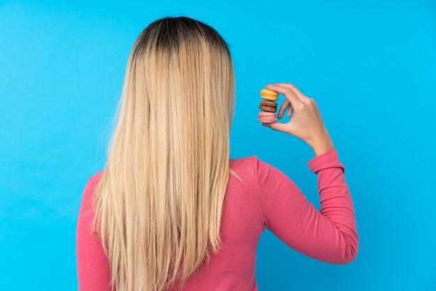 Jonge uruguayaanse vrouw over geïsoleerde blauwe muur die kleurrijke franse macarons in achterpositie houdt