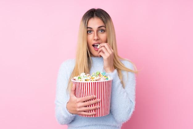 Jonge uruguayaanse vrouw over geïsoleerde roze muur die een grote emmer popcorns houdt