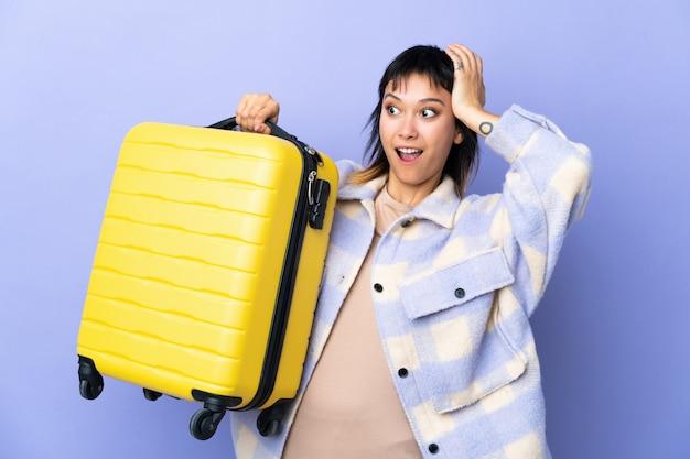Jonge uruguayaanse vrouw over paarse muur in vakantie met reiskoffer en verrast