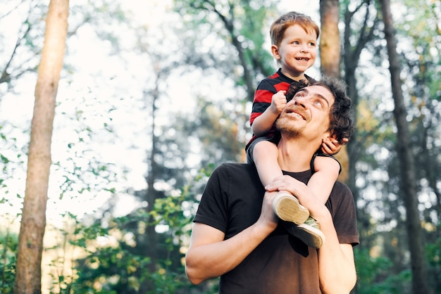 Jonge vader die in de zomer met zijn jonge zoon in het park loopt en het op zijn schouders houdt