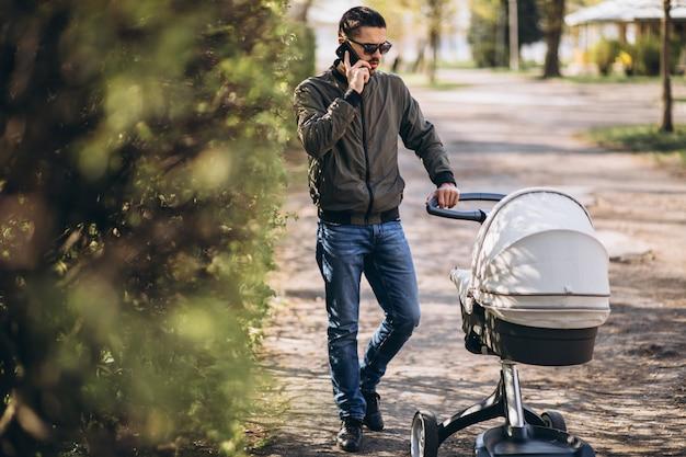 Jonge vader die met kinderwagen in het park loopt