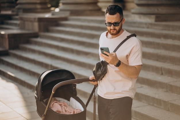 Jonge vader die met zijn baby in een kinderwagen loopt