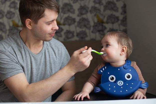 Jonge vader die zijn baby in de keuken voedt. familie tijd en gendergelijkheid concept. levensstijl