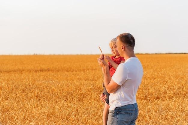 Jonge vader die zijn zoon op gebied van rijpe tarwe achtergrond houdt. weekend buiten op het platteland.