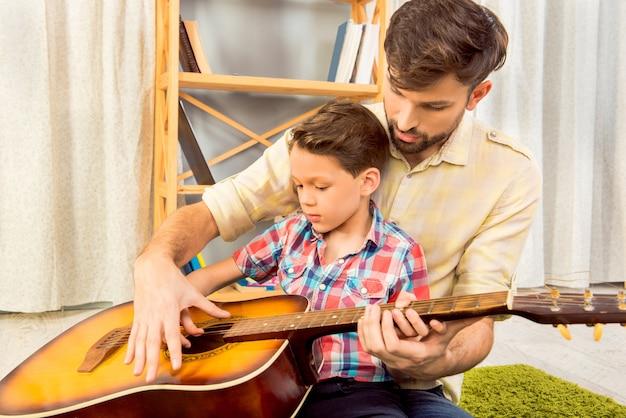 Jonge vader die zijn zoontje leert om op gitaar te spelen