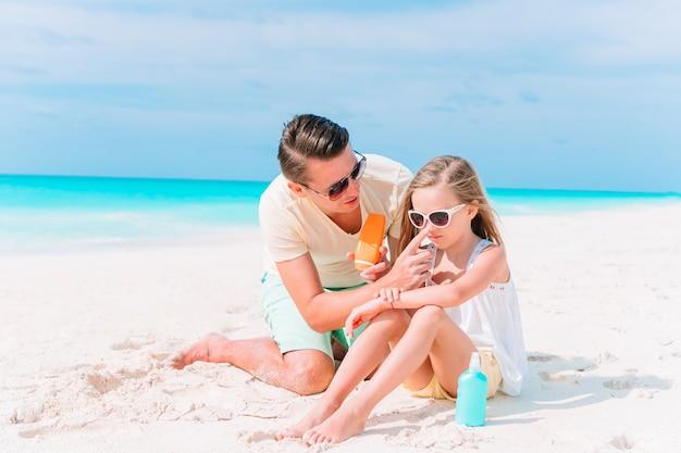 Jonge vader die zonroom toepassen op dochterneus op het strand. zon bescherming