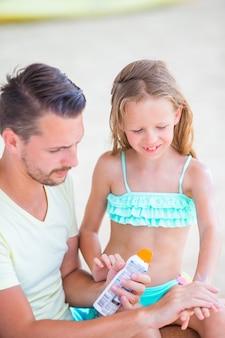 Jonge vader die zonroom toepast op dochter op het strand. zon bescherming