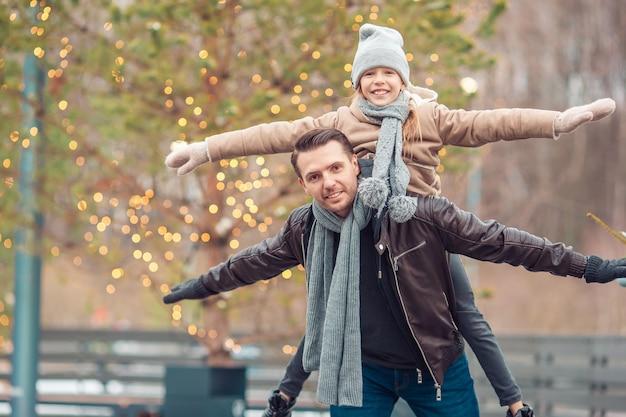Jonge vader en een schattig klein meisje hebben plezier op de ijsbaan buitenshuis