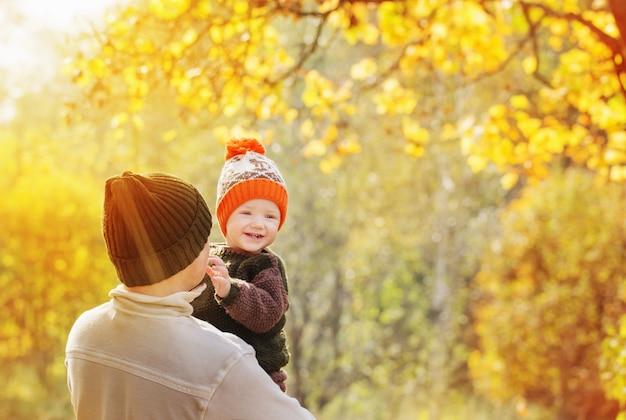 Jonge vader en glimlach zoontje in herfst park