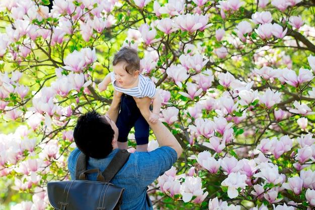 Jonge vader en kind hebben een vrije tijd in de lente bloeiende magnolia-tuin op een zonnige dag.
