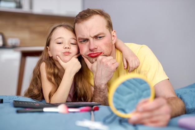 Jonge vader en kind meisje kijken naar reflectie op kleine spiegel met gezichtssamenstelling