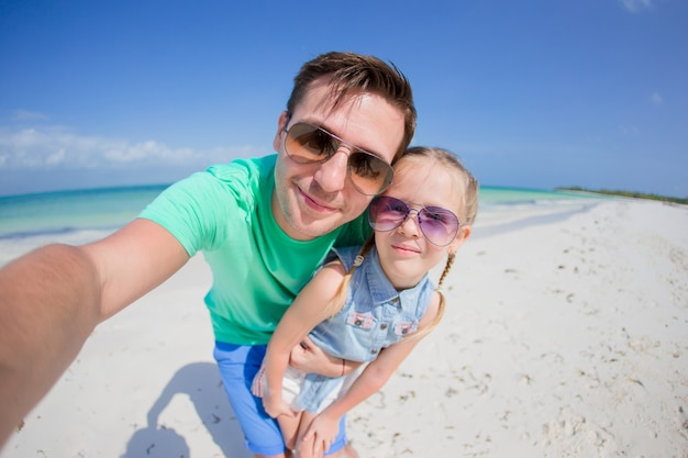 Jonge vader en klein kind nemen selfie foto op het strand