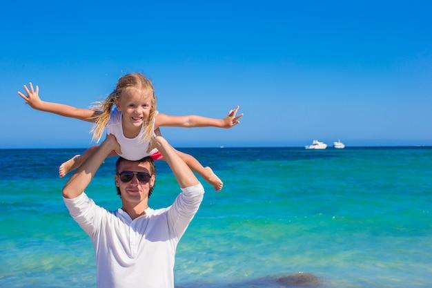 Jonge vader en kleine dochter hebben plezier tijdens tropische strandvakantie