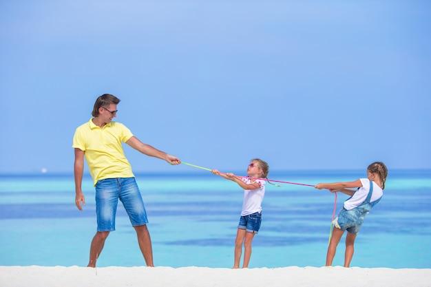 Jonge vader en kleine meisjes hebben plezier samen tijdens tropische vakantie