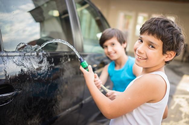 Jonge vader en kleine zonen wassen auto