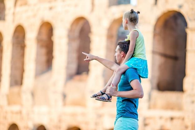 Jonge vader en meisjeachtergrond colosseum, rome, italië