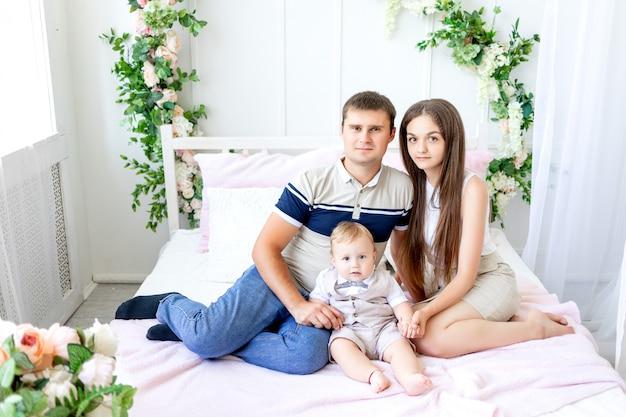 Jonge vader en moeder met een kind, ouders met een kind, familiedag, gelukkige familie