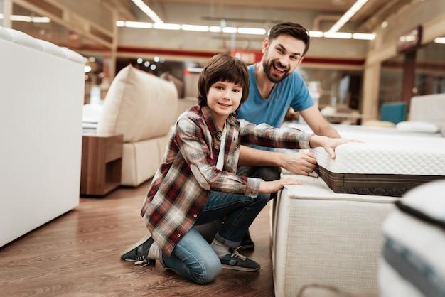 Jonge vader en schattige kleine jongen matras te kiezen