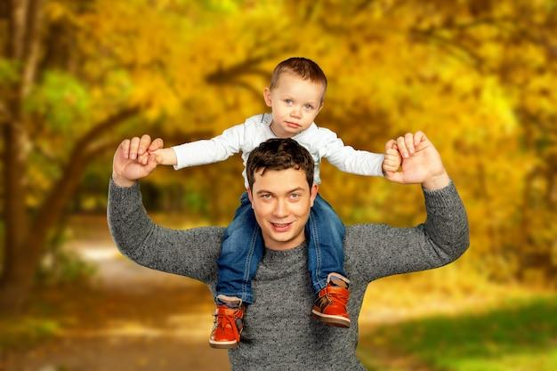 Jonge vader en zijn glimlachende zoon die en van tijd koesteren genieten samen, de dagviering van de vader