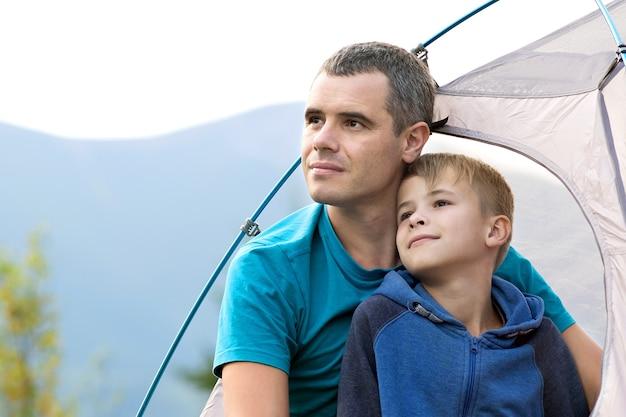 Jonge vader en zijn kindzoon wandelen samen in de zomerbergen. actief familie reizend concept.
