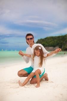 Jonge vader en zijn kleine dochterzitting op tropisch wit zandstrand