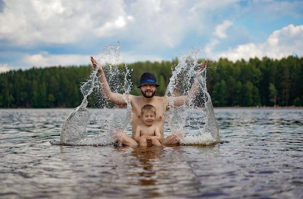 Jonge vader en zijn kleine schattige zoon zitten in het meer in het bos en spetteren