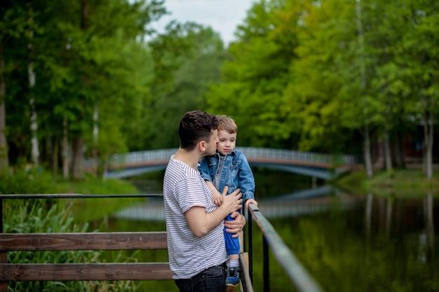 Jonge vader en zijn lachende zoon in het park, knuffelen en genieten van tijd samen, vaderdagviering.