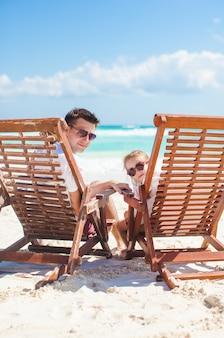 Jonge vader en zijn prachtige dochterzitting op strand houten stoelen die camera bekijken