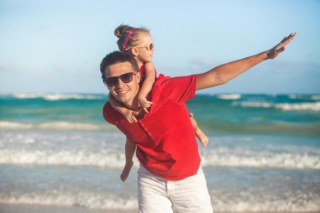 Jonge vader en zijn schattige kleine dochter vliegen als een vogel op tropisch strand