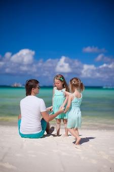Jonge vader en zijn twee kleine kinderen hebben plezier in de buurt van de zee