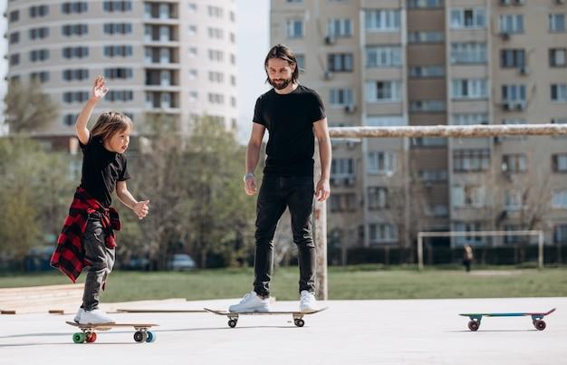 Jonge vader en zijn zoon gekleed in de stijlvolle vrijetijdskleding rijden skateboards op een platform buiten naast het huis op de zonnige warme dag.