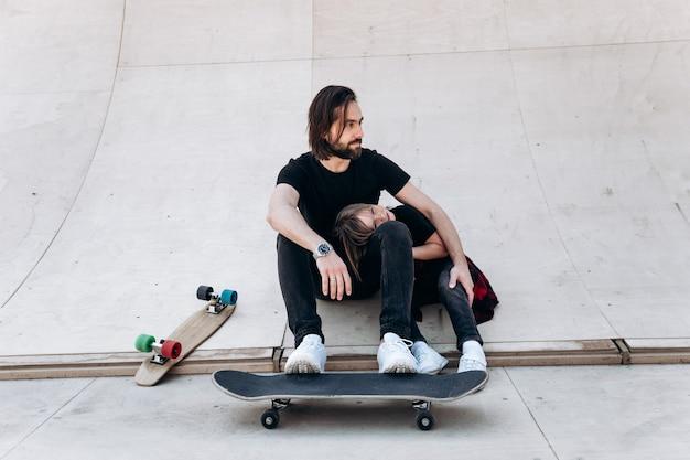Jonge vader en zijn zoon gekleed in de vrijetijdskleding zitten in een omhelzing op de glijbaan in een skatepark naast de skateboards op de zonnige dag.