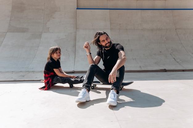 Jonge vader en zijn zoon gekleed in de vrijetijdskleding zitten op de skateboards in een skatepark op de zonnige dag.