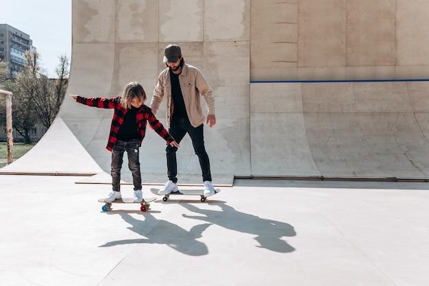 Jonge vader en zijn zoon rijden skateboards in een skatepark met glijbanen buiten op de zonnige dag.