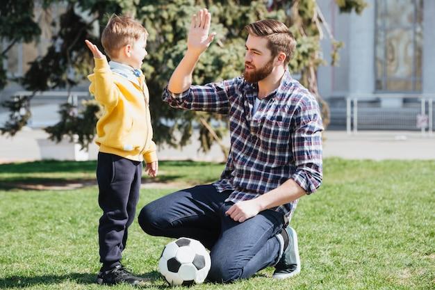 Jonge vader en zijn zoontje geven high five