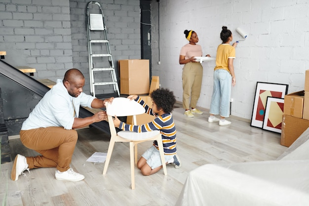 Jonge vader en zoontje monteren houten stoel op de vloer tegen moeder en dochter schilderen muur van woonkamer in witte kleur