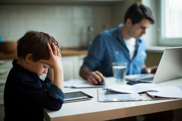 Jonge vader frellancer en kleine jongen die digitale tablet gebruiken