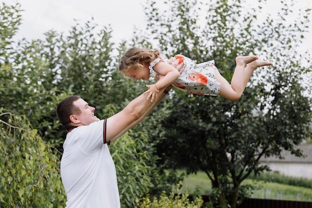 Jonge vader gooit zijn dochtertje hoog in de lucht in het park in zomerdag.