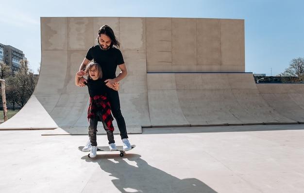 Jonge vader helpt zijn zoontje om op de zonnige dag op het skateboard te rijden in een skatepark.